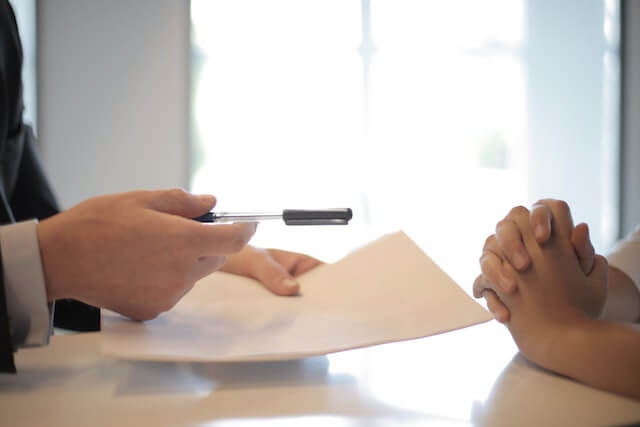 Business person offering pen and paper to client