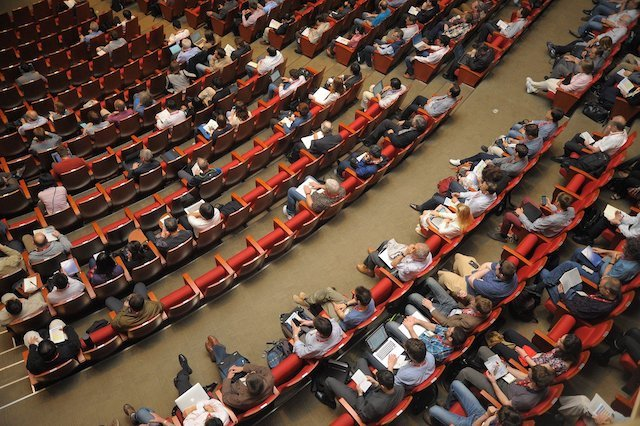 Auditorium filled with people in seats