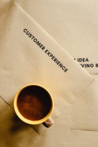 """Coffee cup sitting on paper that reads """"customer experience"""""""
