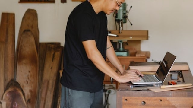 Man working on laptop in a workshop