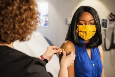 woman in a clinic getting a covid shot min