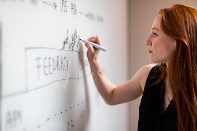 woman writing idea on a whiteboard min