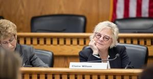 senator Claire Wilson rests her chin on her hand, her head tilting slightly to the side as she listens to someone speak during a committee meeting, a subtle smile on her face