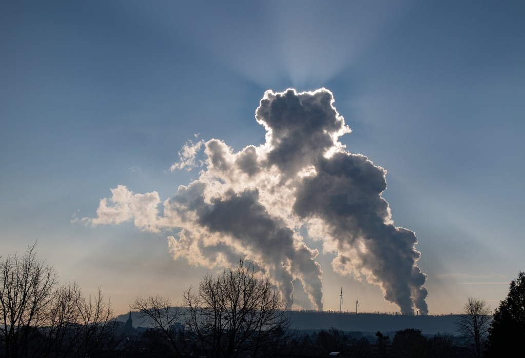 Plumes of smoke rise over a hill. The sun shines from behind the carbon plumes as the rise to the blue sky.