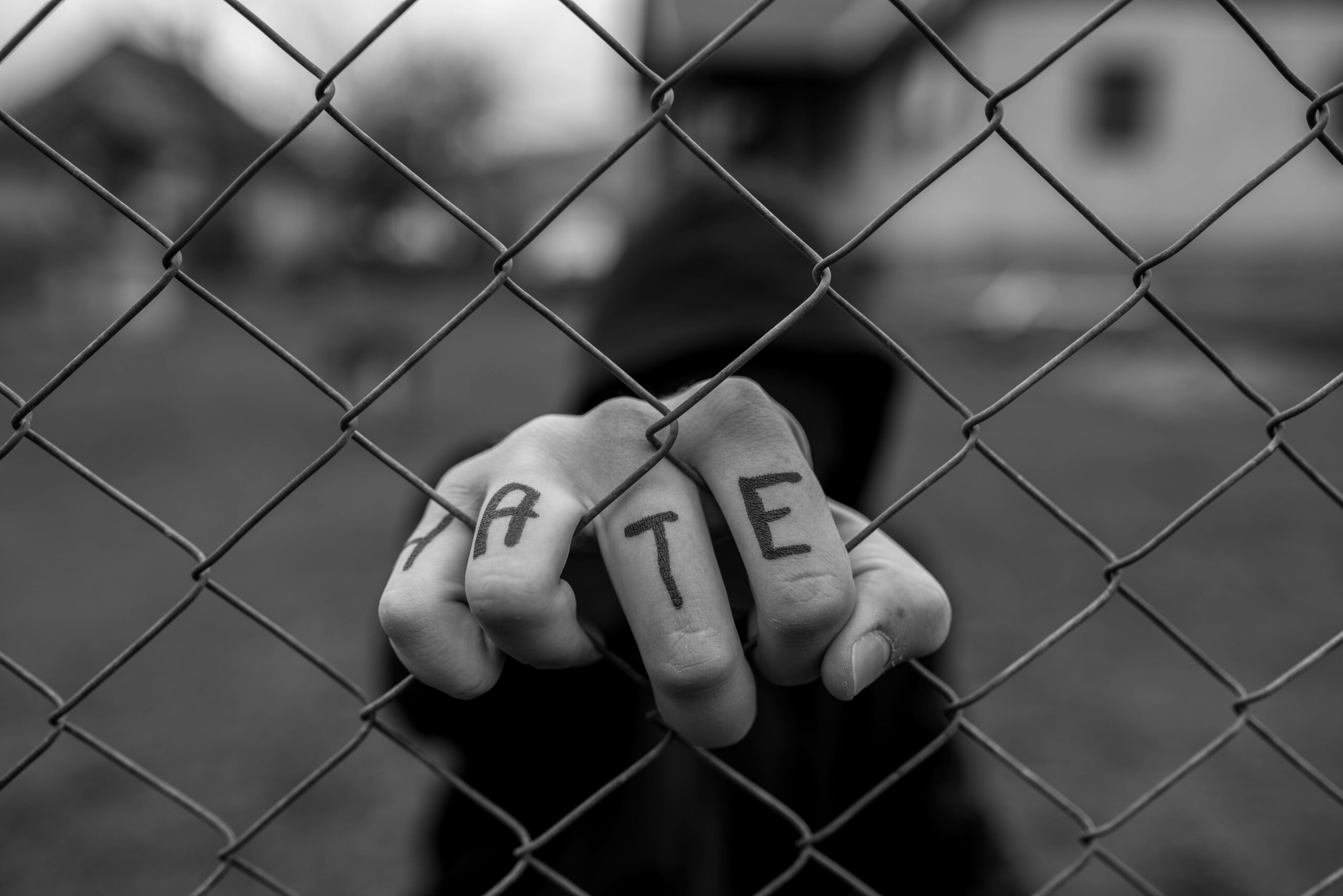 A black and white photo of a hand grasping a wire fence. H A T E is written on the four fingers pulling through the fence.