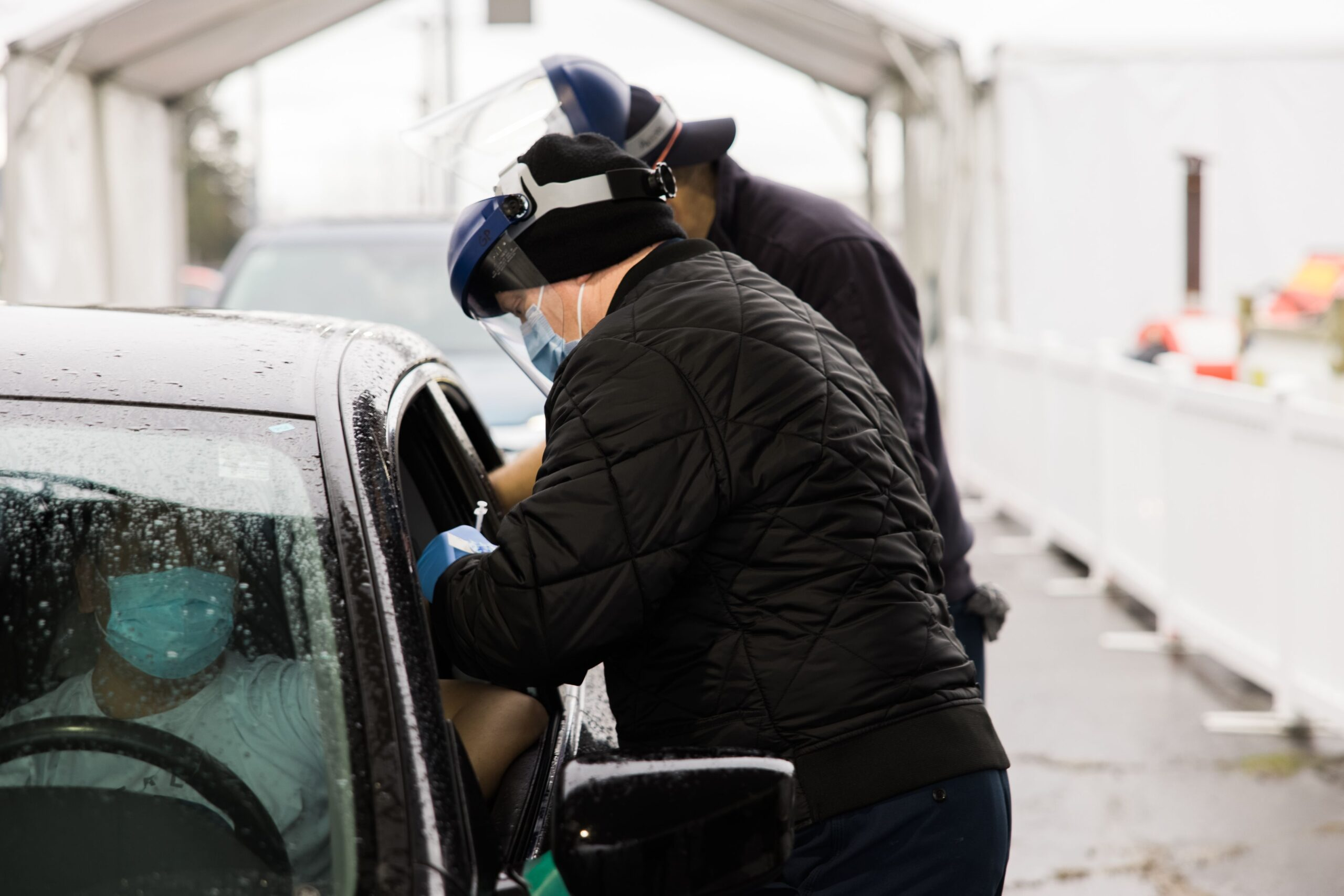 Two males wearing blue surgical masks, clear plastic face shields and black coats stand next to a vehicle. Each male reaches in through a window of the sedan sedan with gloved hands. The manner of the male reaching in to the driver, whose face is largely obscured by a wet windshield, indicates he is administering a shot.