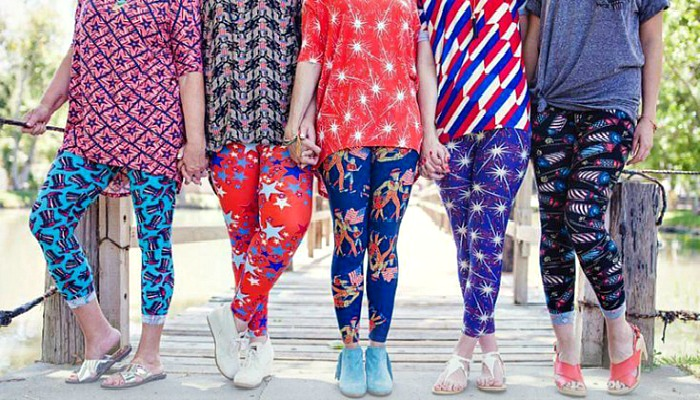 The legs of 5 women in a row, standing on a dock. The women are wearing brightly colored leggings and shirts from the LuLaRoe brand.