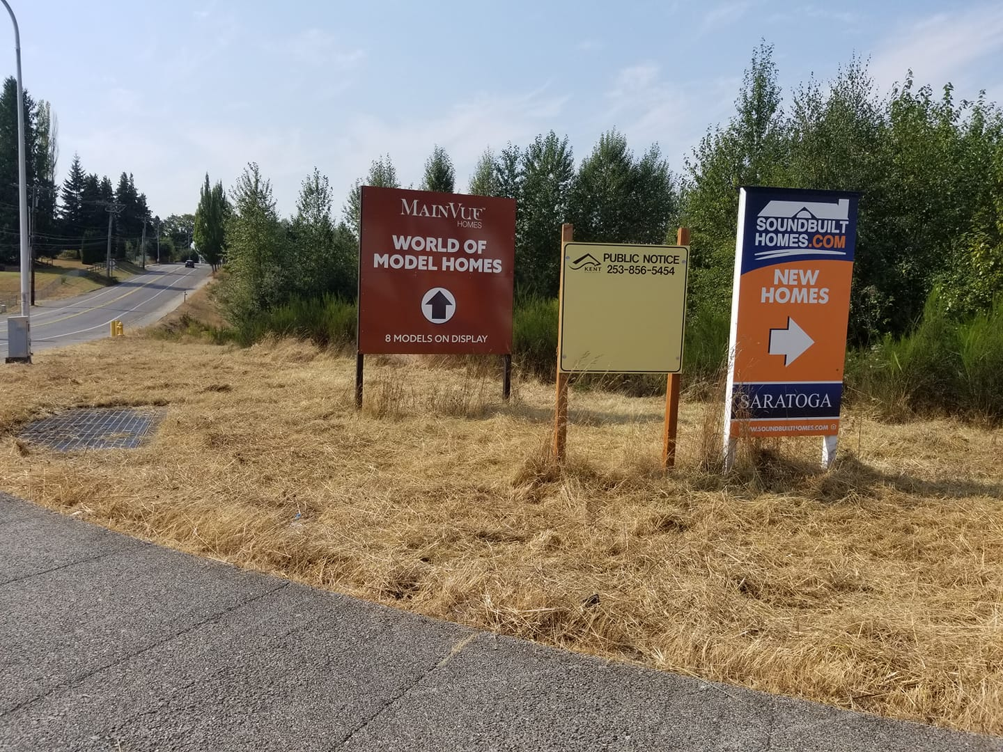 """Three developer signs on an undeveloped corner. The middle sign states """"Public Notice"""" from the City of Kent, but holds no notices."""