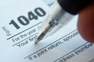 A pen is poised to begin filling out a 1040 tax form