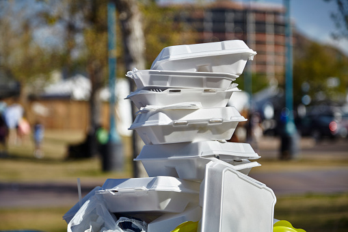 White styrofoam used food containers stacked in trash can in park