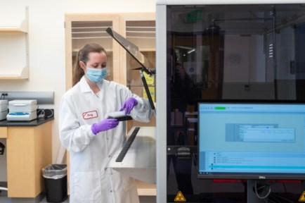 A female scientistic handles a tray of short tubes in front of an open door of a large testing machine. The monitor of the machine faces the camera.