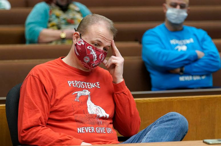 "Tim Eyman sits at in court with his hand to his forehead, looking downward. He wears a red and gray WSU mask and a 'Persistence Never Give Up"" shirt."