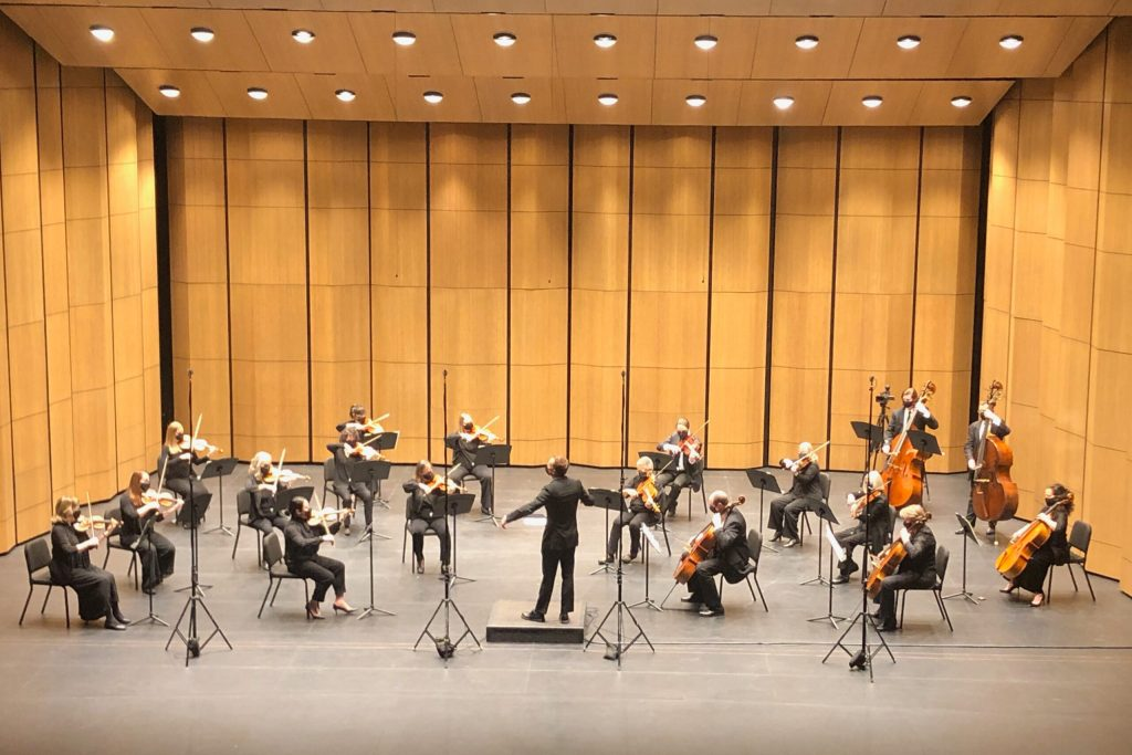 The symphony orchestra, spaced apart, plays on a stage