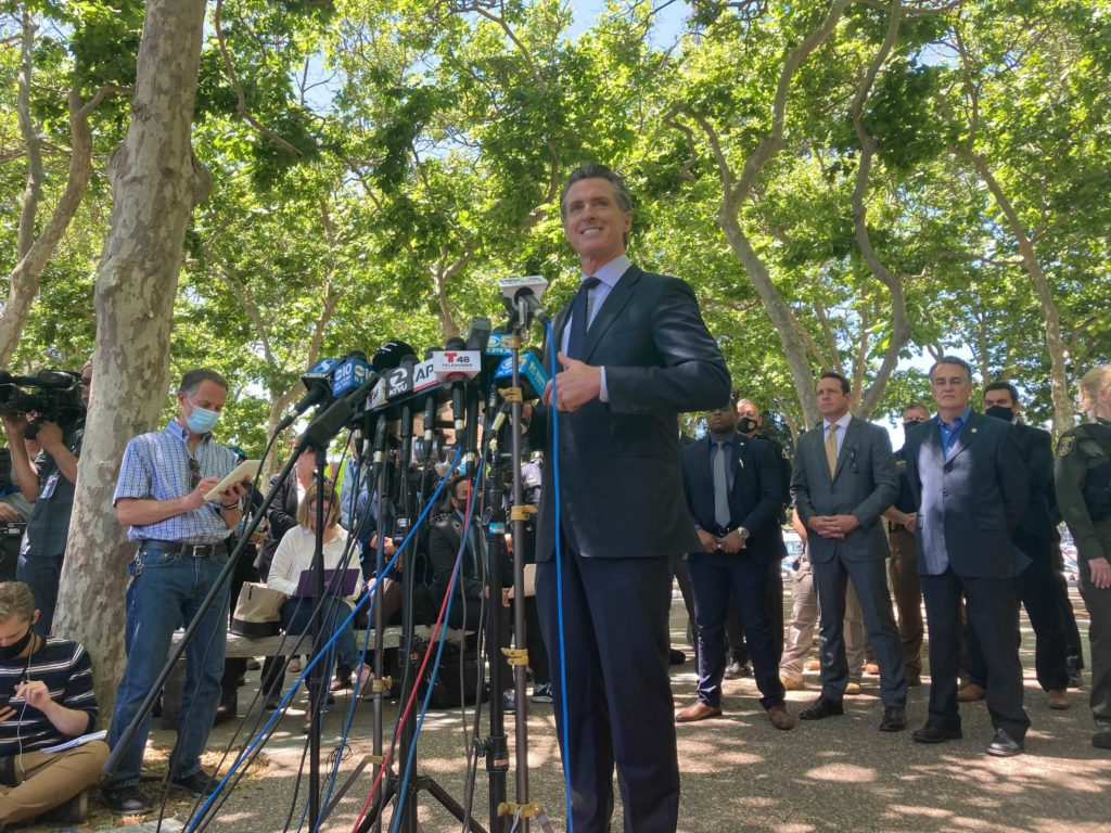 Gov. Gavin Newsom speaks at a stand of media microphones, speaking about the mass shooting at a VTA rail yard in San Jose.