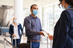 Indian passenger wearing surgical mask showing e-ticket to flight attendant at boarding gate. Young mixed race businessman showing boarding pass on mobile phone to air hostess while wearing protective face mask during covid pandemic. Multiethnic business man in a row with flight reservation hand the phoone to stewardess at airport keeping social distance.