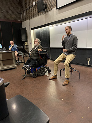 Storyteller, Michael Herzovi sitting in his wheelchair looking at students in a lecture hall. The students are not visible. He is middle-aged, white hair and beard. Professor Carrie Sandahl, a middle-aged white woman, sits in the background, in a chair at the lecture podium, with her hand on her chin smiling at Michael's performance. A white male American Sign Language Interpreter sits near Michael.