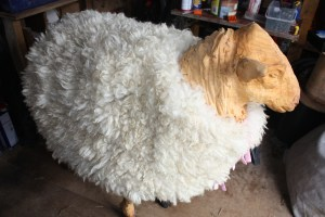 chainsaw carved sheep with felted fleece jacket