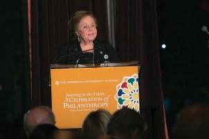 A woman stands at a podium making a speech