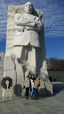 Three Egyptian women in front of a large stone carving of Martin Luther King
