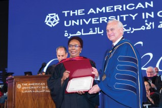 AUC president in a blue gown presents a diploma to a smiling woman with a black gown