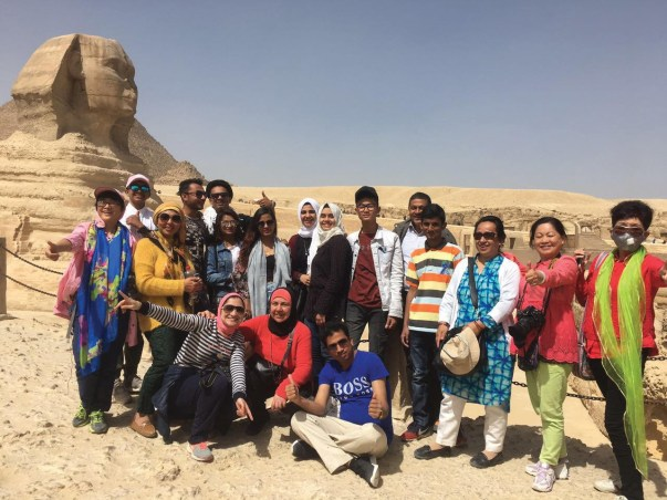 A group of students standing in front of the Sphinx statue in Egypt giving thumbs up and smiling.