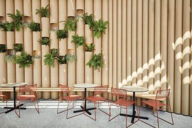 A wall made of paper tubes, with plants fit into it and several tables with chairs in front.