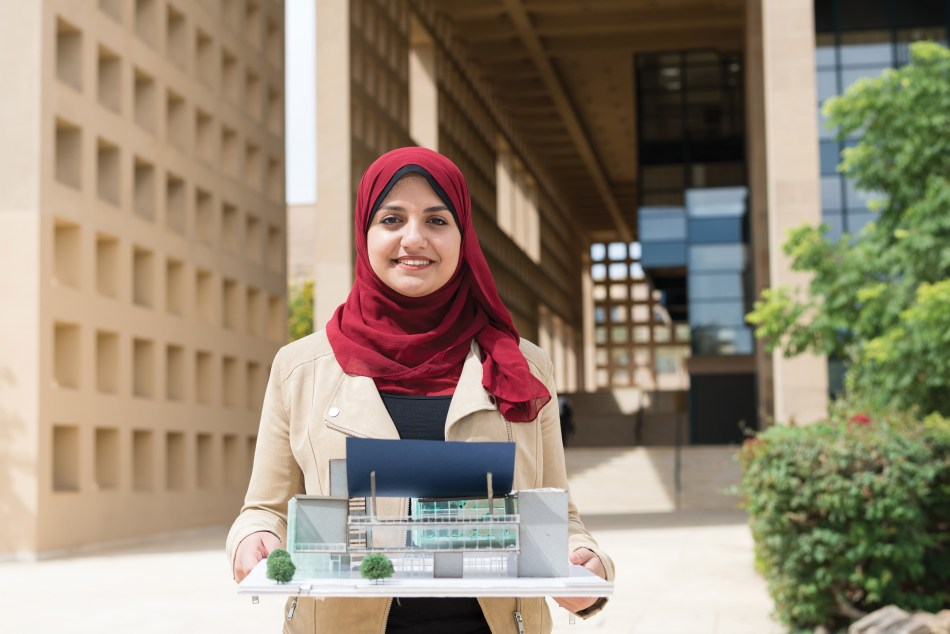 A female student in a red hijab holds her architecture project, a model home, and smiles straight ahead.
