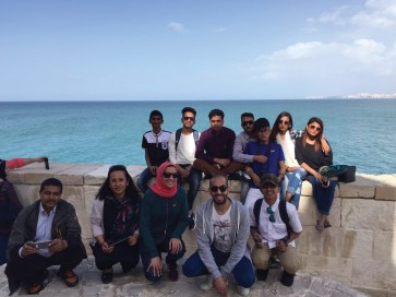 A group of Egyptian and Nepali students sitting on a stone wall in front of the sea