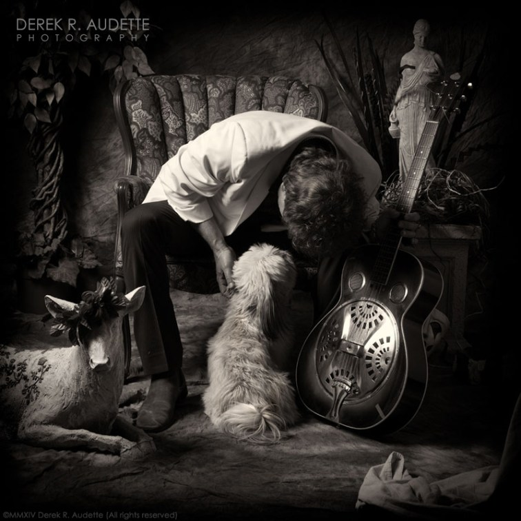 Drew Nelson with small dog and dobro guitar
