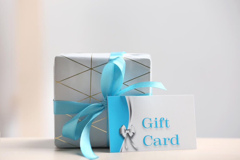 white package with blue ribbon and gift card