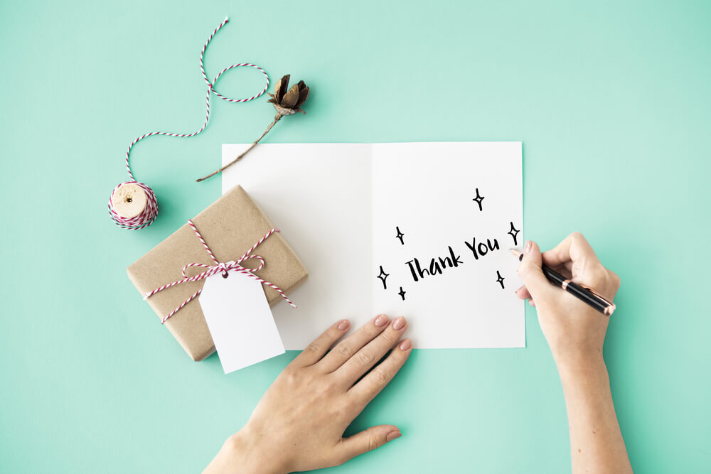woman writing thank you on a note card