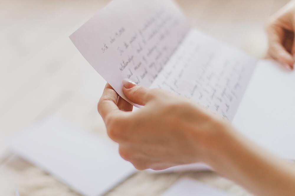 woman hands holding handwritten letter