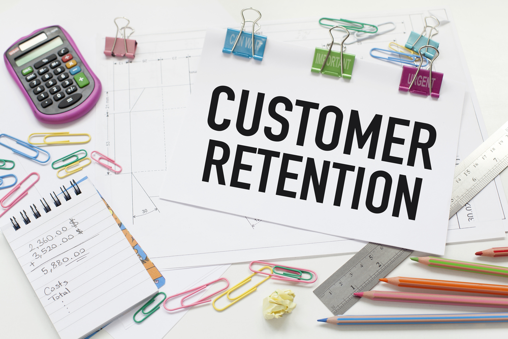 Paper reading Customer Retention surrounded by calculator, papers and other supplies