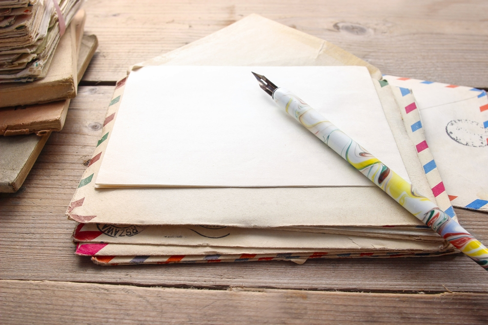 stack of old envelopes with pen