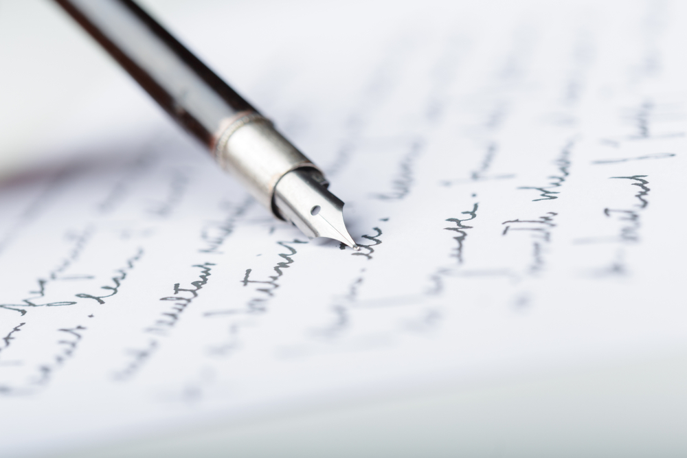 fountain pen laying on a stack of handwritten letters
