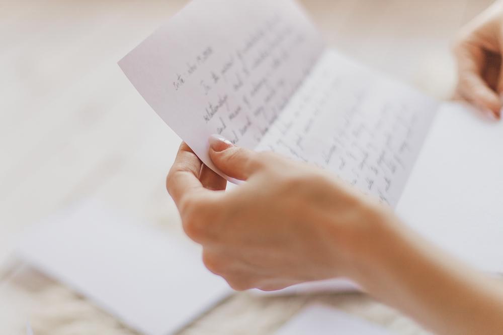 woman's hands holding handwritten letter