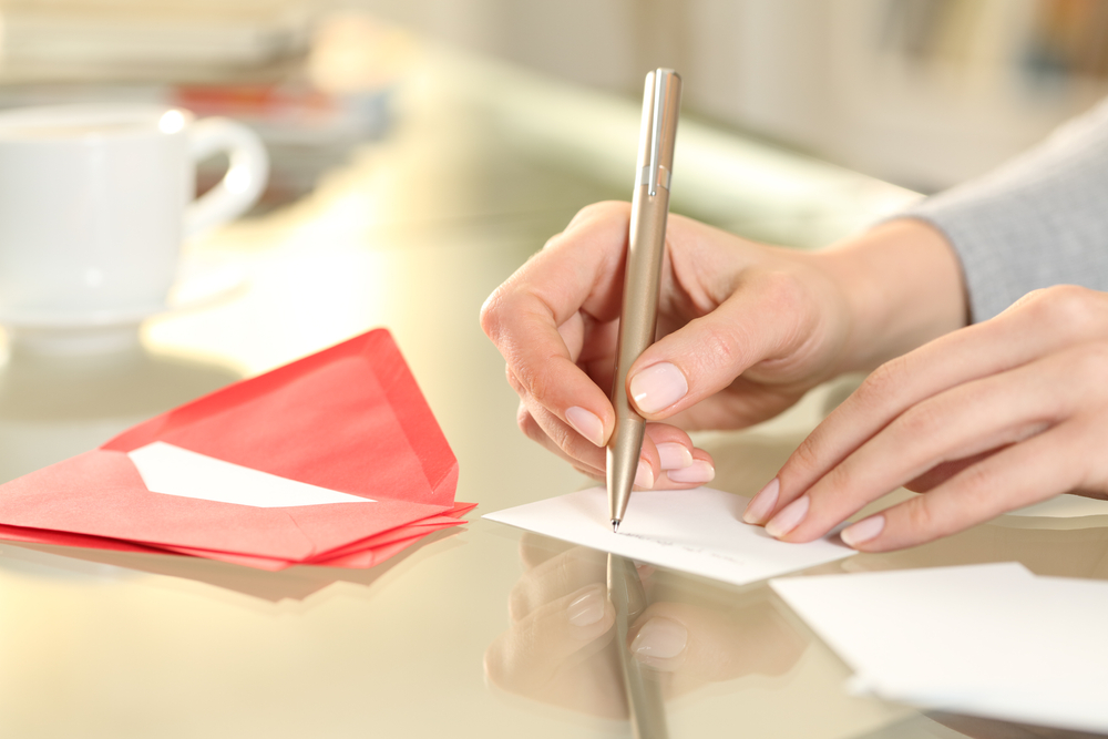 woman handwriting a letter with red envelope laying nearby