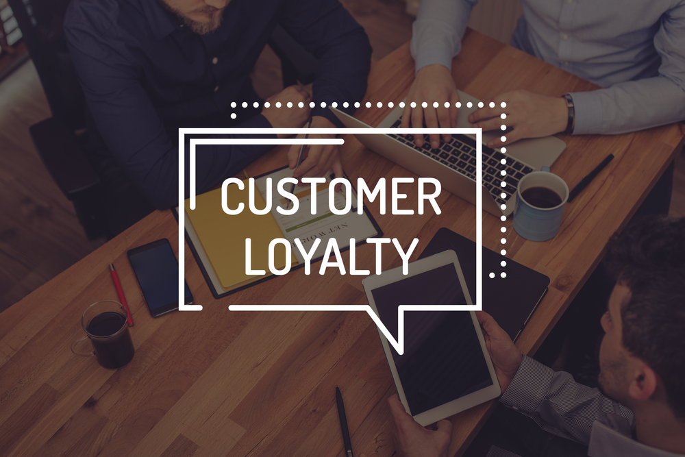 wood table with words customer loyalty on top