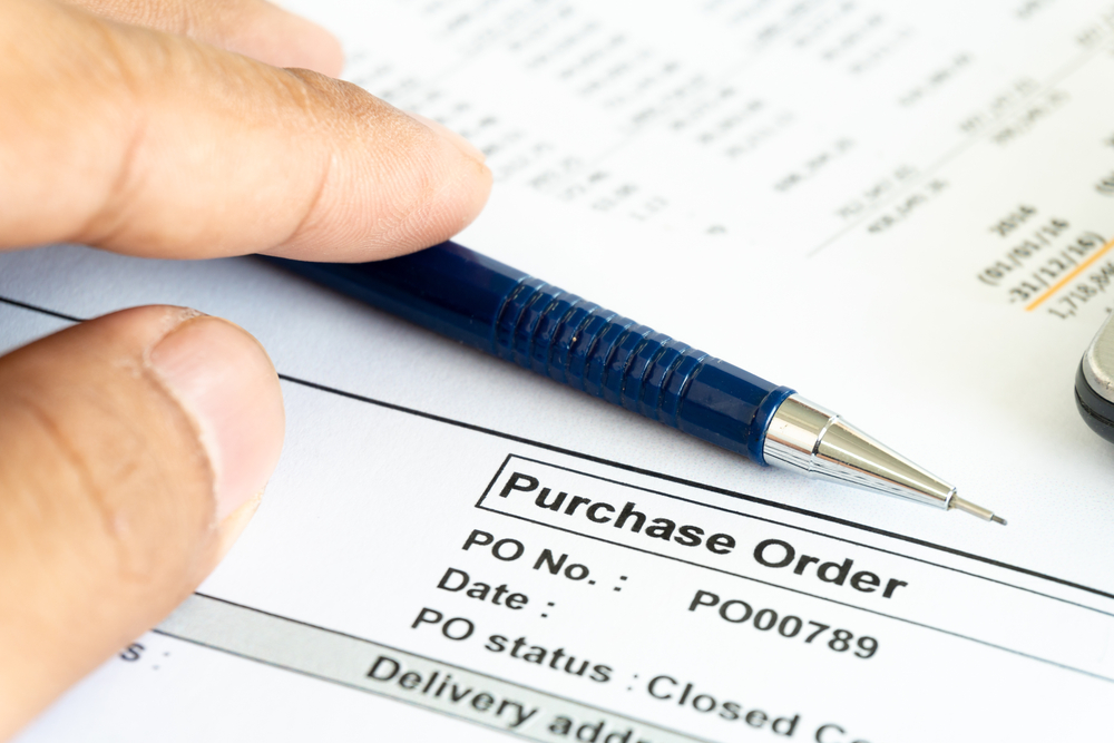 man holding pen over Purchase Order document