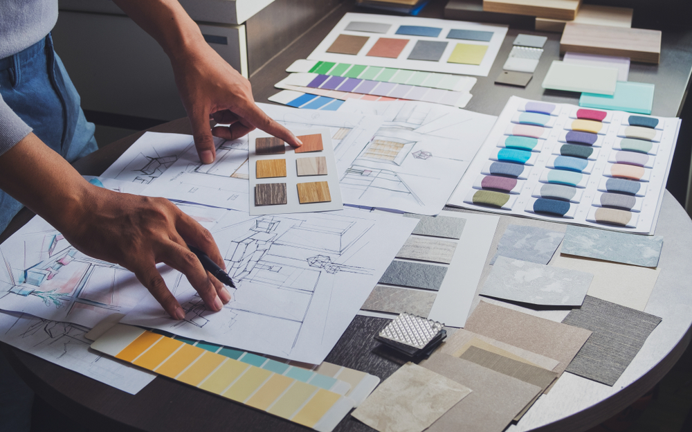 man surrounding by designing tools like color swatches