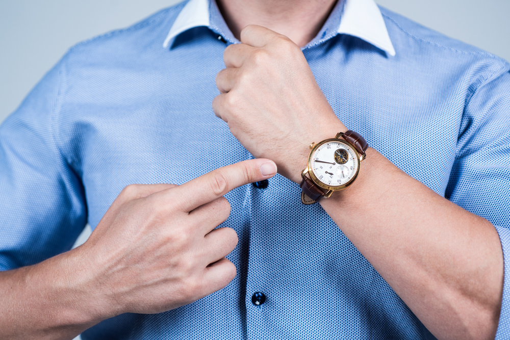 man in button up shirt pointing to watch