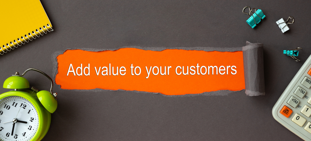 Text Add value to your customers - appearing behind torn brown paper.