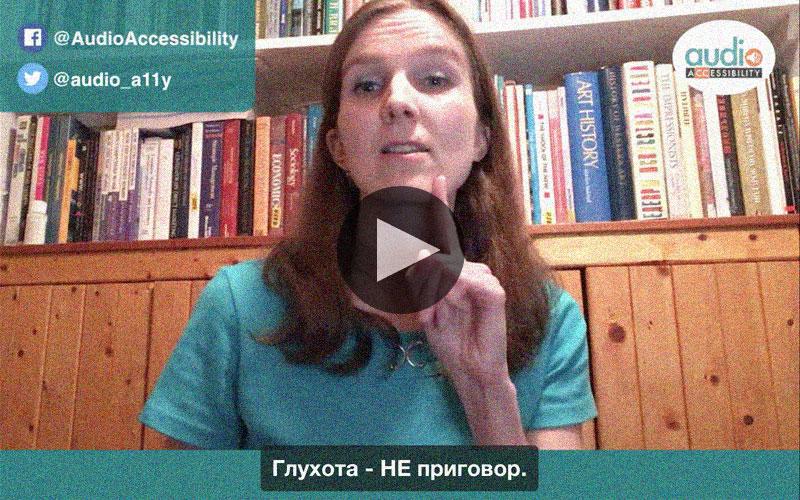 Глухая брюнетка в зеленой майке говорит перед камерой. За ней книжный шкаф. Перед ней субтитры: Глухота - НЕ приговор.
