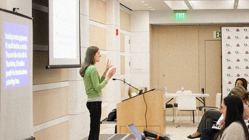 Svetlana speaking in sign language in front of audience