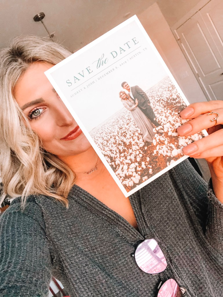 Save The Date Ideas featured by top US lifestyle blogger Audrey Madison Stowe; Image of woman holding a save the date card.