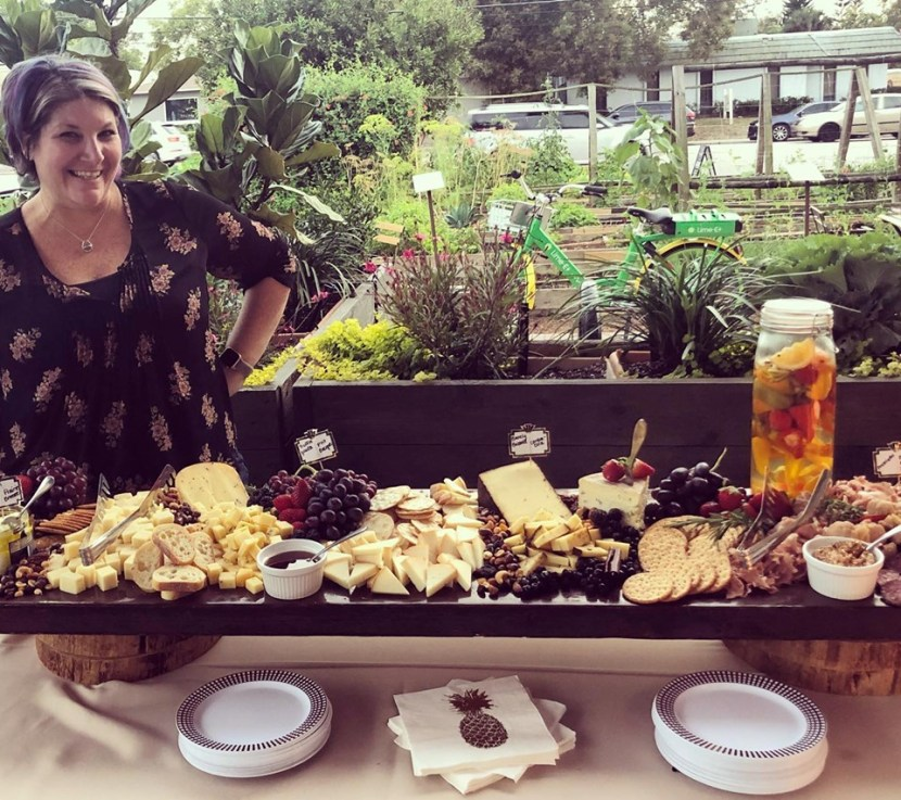 A woman standing by a large platter of assorted cheeses, bread and fruits