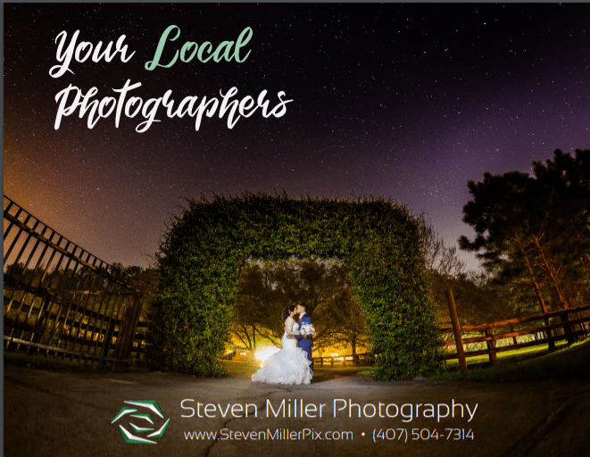 A wedding couple under a garden arch with a night sky