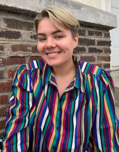 Marz in a striped shirt in front of a brick wall