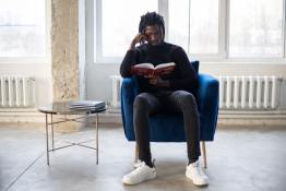A Black man sitting in a blue chair reading a book. A round side table is to the left.