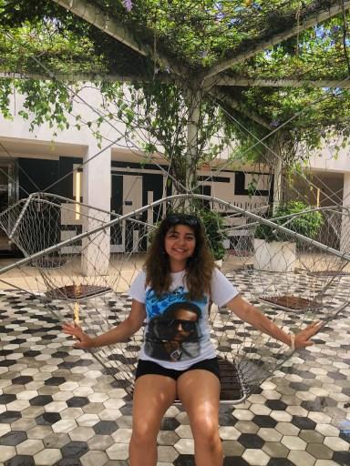 Photo of Ashley Olanda-Oliva sitting outside with a tree in the background.